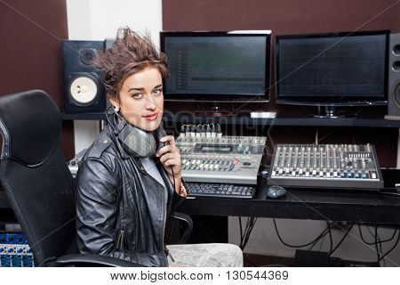 Confident Young Woman Sitting At Mixing Desk