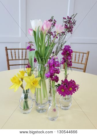 Colorful flowers in clear vases grouped on a table with two  chairs on either side against a light gray painted wall