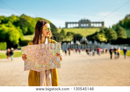 Young female tourist traveling with paper map in Schoenbrunn palace with Gloriette building on the background