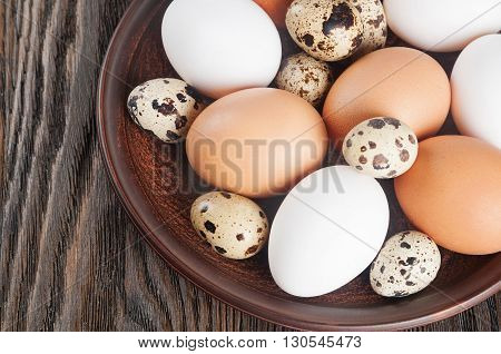 Quail and chicken eggs in a clay plate on a wooden background