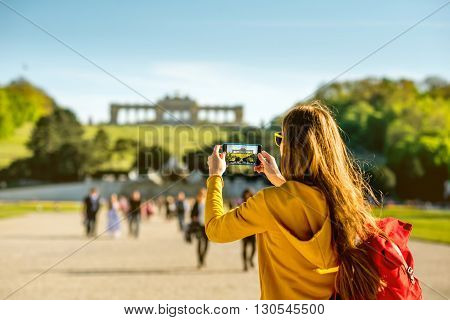 Young female tourist photographing with phone Gloriette building in Schoenbrunn palace in Vienna