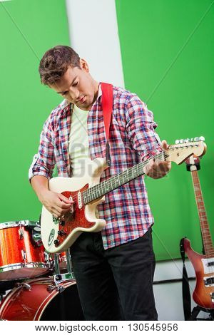 Male Guitarist Performing In Recording Studio