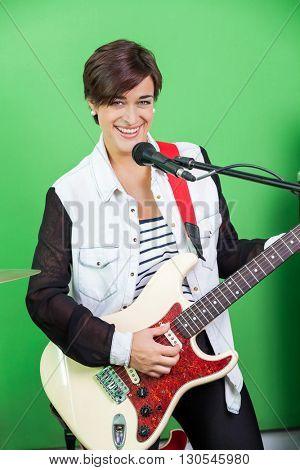 Female Signer Playing Guitar While Singing In Recording Studio