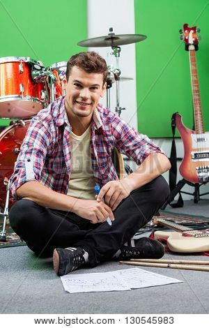 Male Drummer Holding Sketch Pen While Sitting On Floor