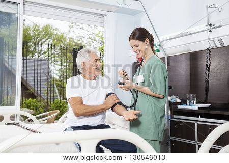 Nurse Examining Blood Pressure Of Senior Man In Rehab Center