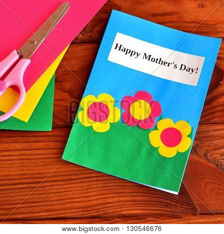 Greeting card Happy mother's day - easy children's crafts. Scissors, paper sheets on brown wooden background