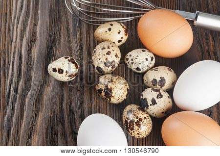 Quail and chicken eggs on a wooden background. White and brown chicken eggs.
