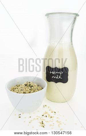 Hemp milk and hemp hearts in bowl isolated on white background