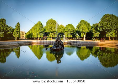 VIENNA, AUSTRIA - CIRCA APRIL 2016: Fountain in Schonbrunn gardens. Schonbrunn gardens are one of the most important historical places in Austria. Long exposure image technic with glossy water