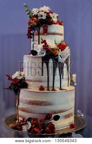 White tree-tiered cake with flowers and chocolate, berries