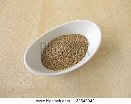 Dried bakers yeast in small bowl on table
