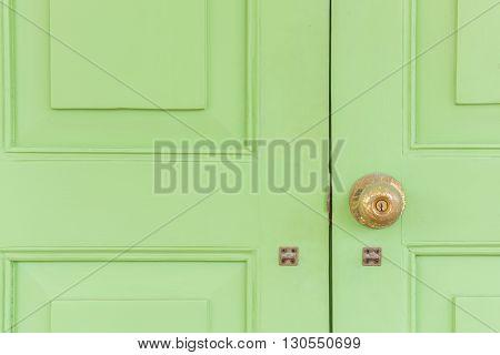 Vintage golden knob on the green wood door. Croped composition.