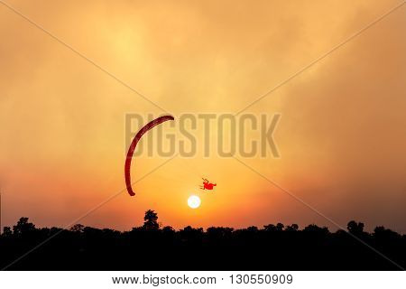 Silhouette of paraglider flying over trees at sunset