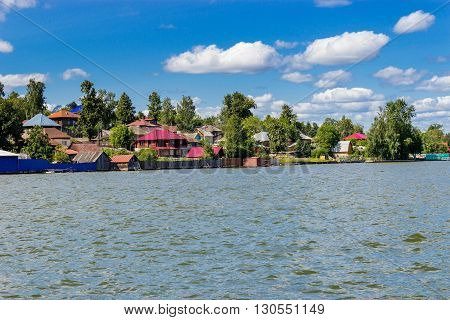 Rural houses on the lake in the summer. Russia