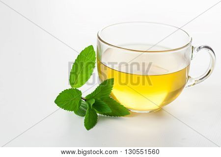 Glass of mint tea on white mint leaves on the side