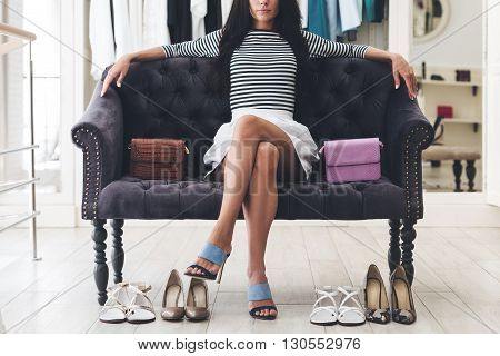 Confident in her choice. Part of beautiful young woman keeping legs crossed at knee while sitting on sofa at the shoe store