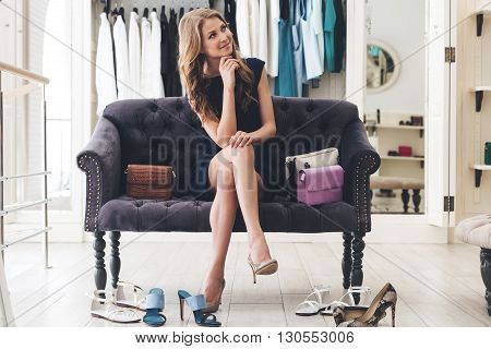 Maybe I need another pair? Beautiful young woman looking thoughtful while sitting on sofa at the clothing store