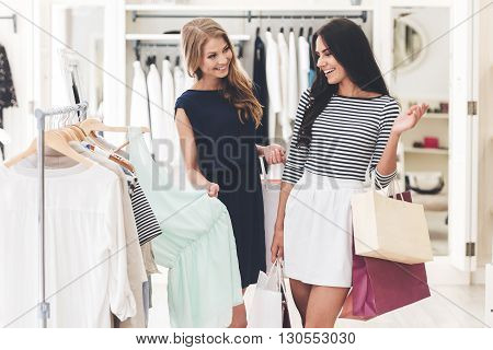 Maybe this dress? Two beautiful women with shopping bags looking at each other with smile while standing hear hanger at the clothing store