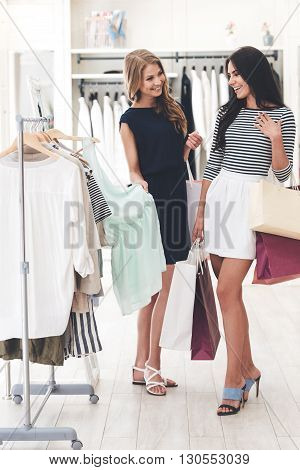 Do you like this color? Two beautiful women with shopping bags looking at each other with smile while standing hear hanger at the clothing store