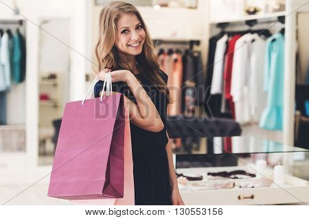 Satisfied with her shopping. Beautiful young woman with shopping bags looking at camera with smile while standing at the store