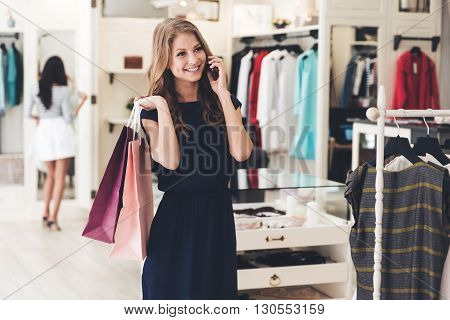 That was great shopping! Beautiful young woman with shopping bags talking on mobile phone with smile while standing at the clothing store