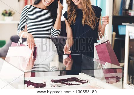 Maybe this is one? Close-up of two beautiful women with shopping bags looking at lingerie showcase with smile while standing at the store