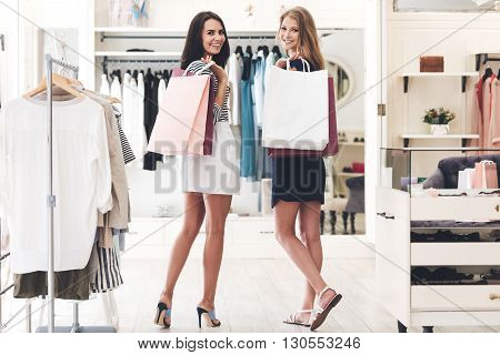 Shopping with bestie. Rear view of two beautiful women with shopping bags looking at camera with smile while walking at the clothing store