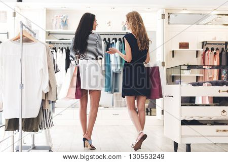 Shopping therapy in action. Rear view of two beautiful women with shopping bags looking at each other with smile while walking at the clothing store
