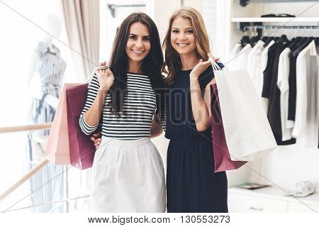 Shopping with friend is pure pleasure! Two beautiful women with shopping bags looking at camera with smile while standing at the clothing store