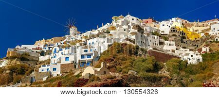 Panoramic view of windmills and white houses in Oia or Ia on the island Santorini, Greece