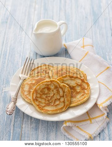 Freshly baked pancakes with sour cream on a light blue background