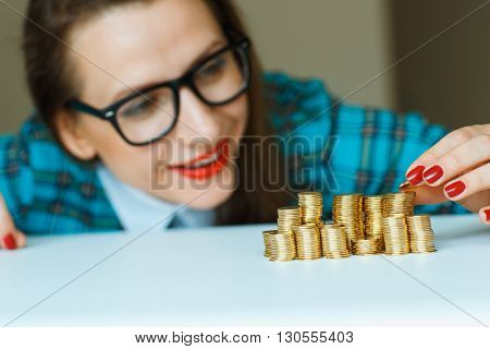 Saving woman stacking gold coins into columns