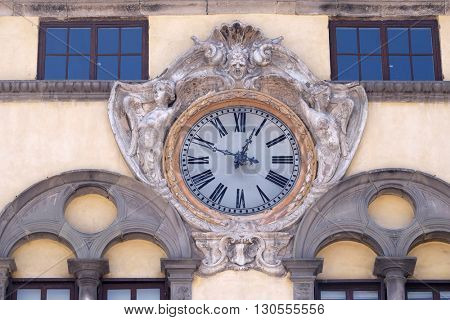 LUCCA, ITALY - JUNE 06, 2015: Clock on facade of ancient palace over the square of San Michele in Foro in Lucca, Italy, on June 06, 2015