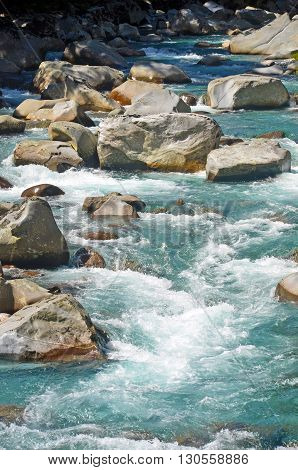Crystal clear water of an alpine river flowing around rocks