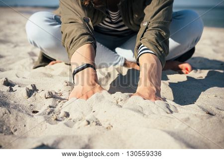 Girl Sitting On The Beach And Touch The Sand