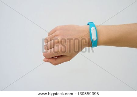 Blue fitness tracker closeup on a female hand. White background not isolated.