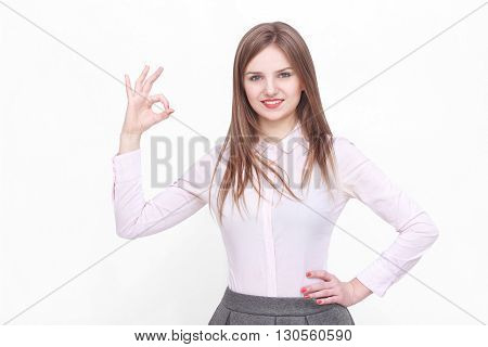 Young succesfull businesswoman gesturing ok or yes on isolated background