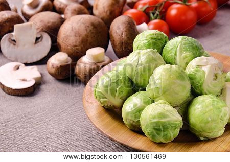 Several heads of fresh wet brussels sprouts on a wooden plate, cherry tomatoes on a linen fabric .