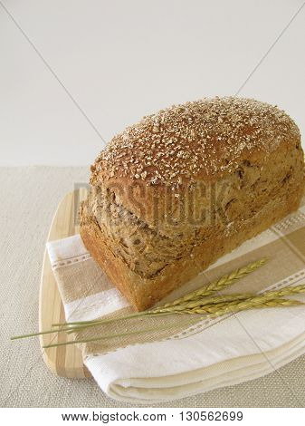 Homemade spelt bread on wooden board on table