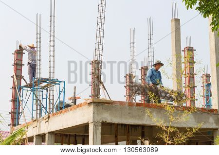 CHAINGMAI, THAILAND - April 15, 2016 : Construction workers fabricating column timber form work and reinforcement bar at the construction site in Chaingmai Thailand
