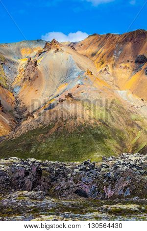 Travel to Iceland in the July. Summer volcanic tundra. Incredible shades of rhyolitic mountains - yellow, orange, green and blue