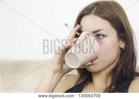 Woman holding cigarette and a cup of coffee in hand and sit on the sofa conceived at home