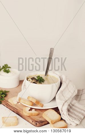 delicious creamy soup with croutons and greens on Boards .Toned photo