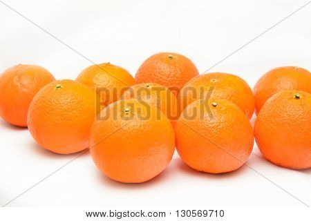 many fresh unrefined organic mandarin (tangerines) over white