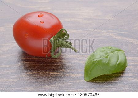 Cherry tomatoes on a dark table. A bunch in drops of water. Basil leaf.