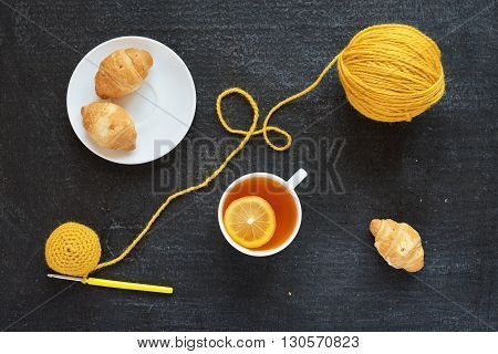 Lemon tea, yellow crocheting and croissants on black background