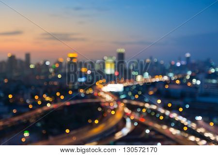 Abstract blurred bokeh lights, city downtown background and highway after sunset