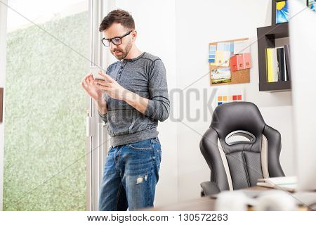 Designer Using A Smartphone In His Office