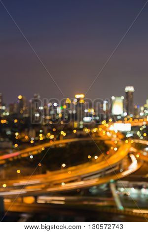 Abstract blurred lights highway interchanged and office building background, night view