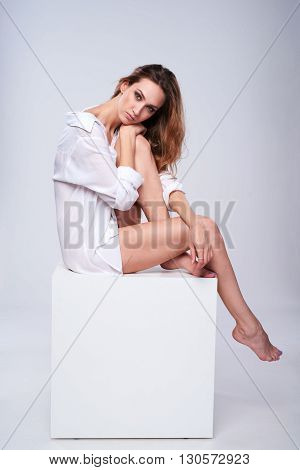Full length beautiful leggy woman wearing boyfriend white shirt sitting on white box with blank empty copy space
